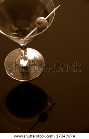 Cocktail with olive close-up over reflective background - stock photo