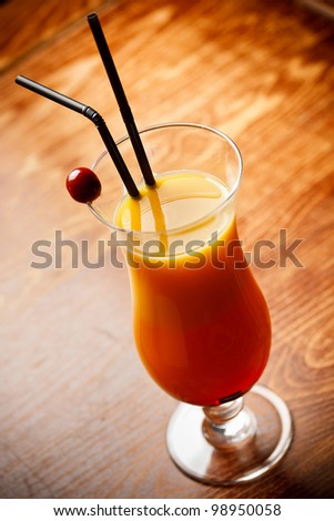 Cocktail with orange Juice on bar tabel, cherry and straw decoration