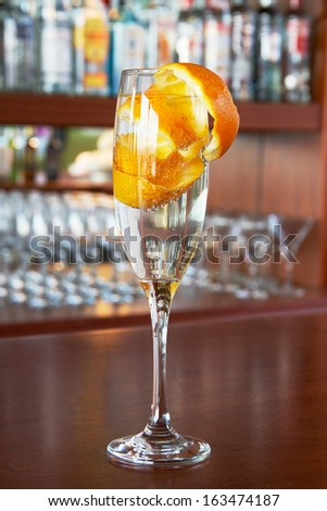 cocktail with orange peel garnish on the bar on a background bottles