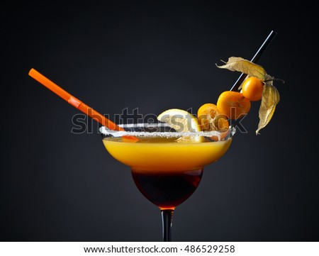 Cocktail with physalis,kumquat and lemon on a dark background