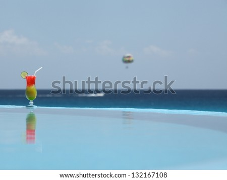 Cocktail with straw at the tropical ocean background
