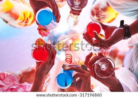 Cocktails held by friends at party