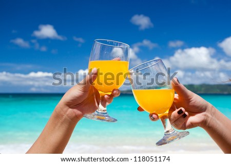 Cocktails on beach in female hands, cheers - stock photo