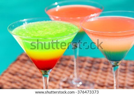 Cocktails on swimming pool background