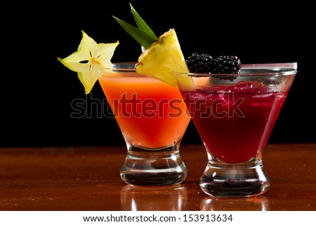 cocktails served in  stemless martini glasses garnished with a pineapple slice, blackberries and star fruit - stock photo