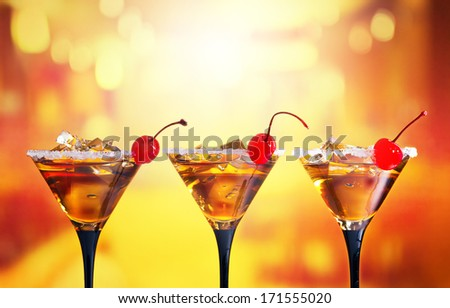 cocktails with cherry and ice in bar - stock photo