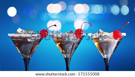 cocktails with cherry and ice on blue background - stock photo
