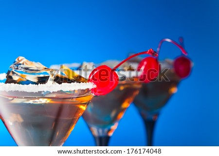 cocktails with cherry and ice on blue background