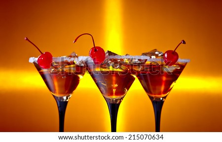 cocktails with cherry and ice on yellow background - stock photo
