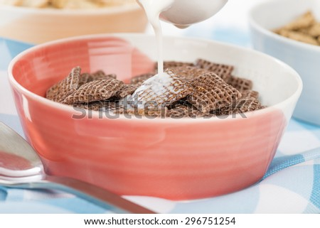 Coco Shreddies - Milk being poured in a bowl with chocolate flavoured cereals.