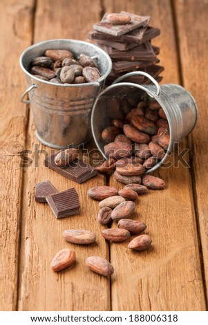 Cocoa beans in two tin buckets and broken dark chocolate - stock photo