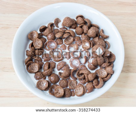 Cocoa cereal with milk  on a wooden table.