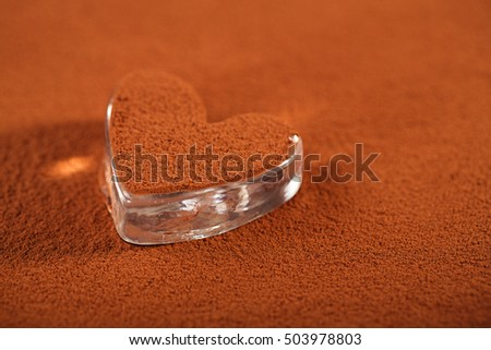 cocoa chocolate powder with dusted heart shaped glass, perfect color and background