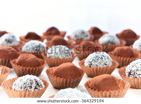 Cocoa dusted and coconut flakes coated homemade chocolates arranged in a regular pattern against a white background - stock photo