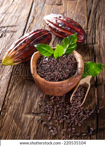 Cocoa pod with bowl on a dark wooden table, close-up. - stock photo