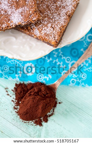 cocoa powder and brownies on background