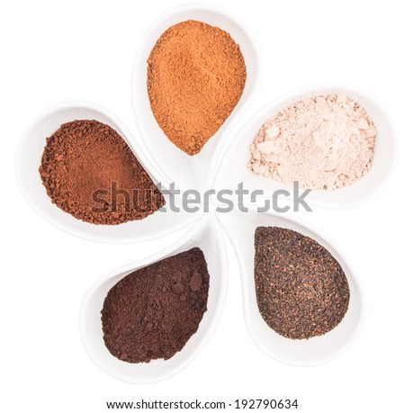 Cocoa powder, dried tea leaves and grounded coffee in a white ceramic container over white background - stock photo