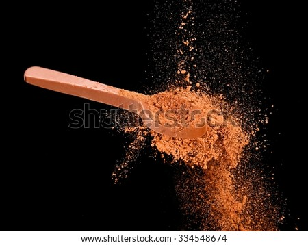 Cocoa powder explosion from a chocolate teaspoon - stock photo