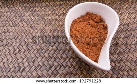 Cocoa powder for making drinks in a white ceramic container over wicker background