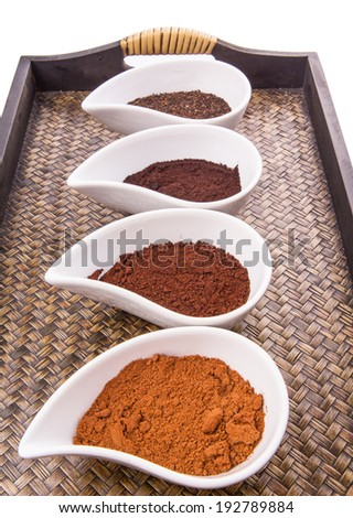 Cocoa powder, ground coffee and dried tea leaves in a white ceramic container in a wicker tray
