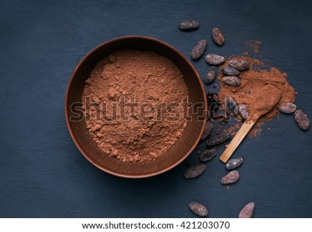 Cocoa powder in a bowl on the black background - stock photo