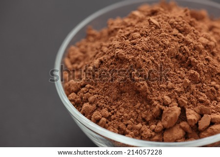 Cocoa powder in a glass bowl on black background. Closeup. - stock photo