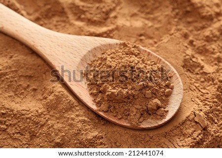 Cocoa powder in a wooden spoon on cocoa powder background. Close-up.