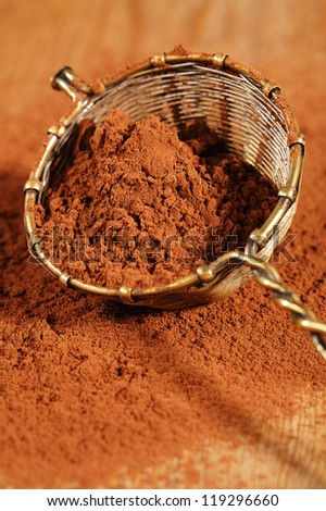 cocoa powder in old rustic style silver sieve, shallow dof - stock photo