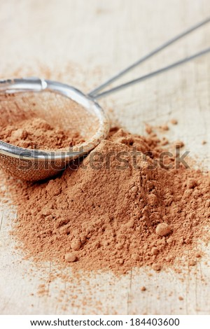 Cocoa powder in silver sieve on a rustic wooden board