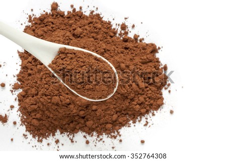 Cocoa powder in spoon on cacao powder background with empty place for your text. - stock photo
