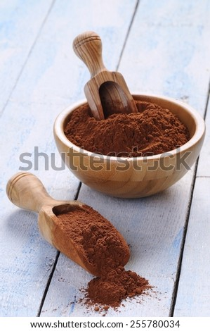 Cocoa powder on wooden table in the kitchen - stock photo