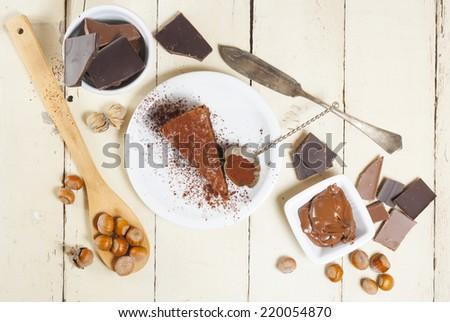 cocoa powder topped hazelnut cake and ingredients on bright wood background - stock photo