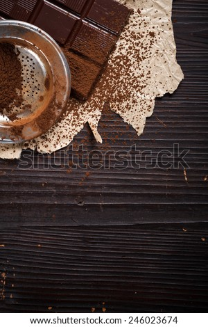 Cocoa powder with sieve on chocolate bar, rustic background - stock photo