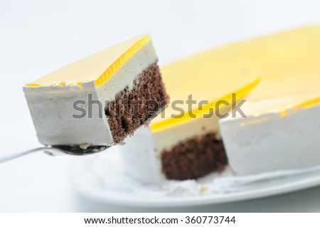 cocoa sponge cake with yellow gelatin on metal spoon, tart on white plate, patisserie, photography for shop, birthday cake - stock photo