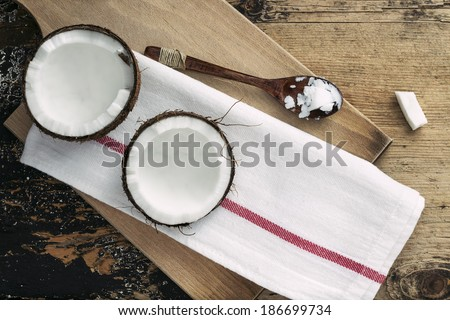 Coconut and coco oil on wooden background - stock photo