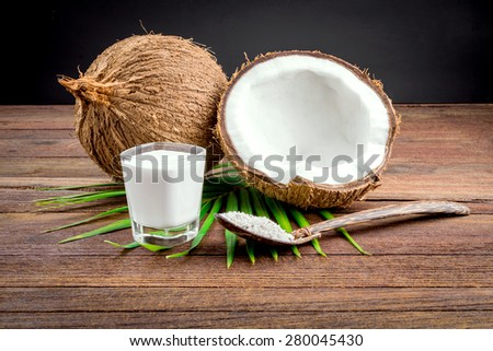 Coconut and coconut milk in glass on wooden table - stock photo