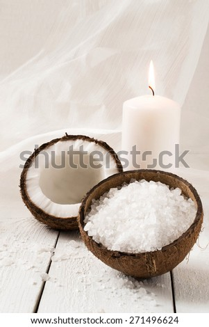 Coconut and spa products: sea salt, coconut oil, coconut aroma with candle on white background. Selective focus - stock photo