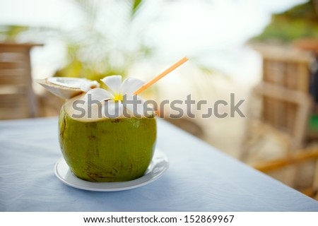 Coconut, beach cafe, plumeria on table with blurry background