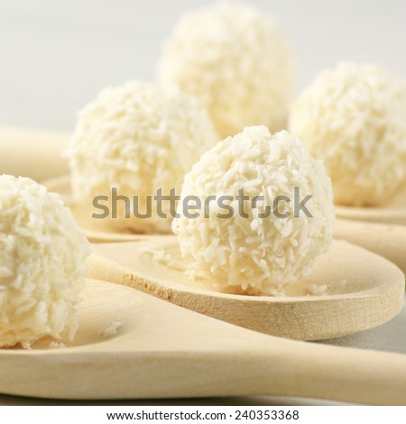 Coconut candies in wooden spoons.