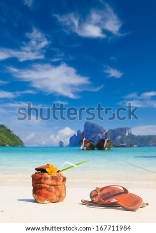 Coconut cocktail with drinking straw and sandals on the beach at Ko Phi Phi - stock photo