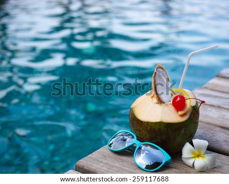 Coconut cocktail with drinking straw by the swimming pool with the sunglasses - stock photo