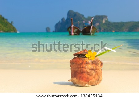 Coconut cocktail with drinking straw on the beach in Thailand - stock photo