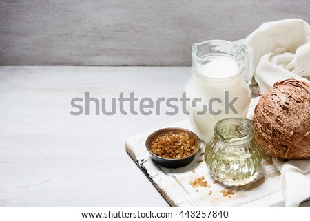 Coconut, coconut milk, sugar and oil on the white wooden table. Ingredients. Organic food concept. Still Life