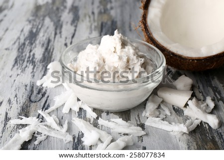 Coconut coconut oil and flakes on wooden background - stock photo