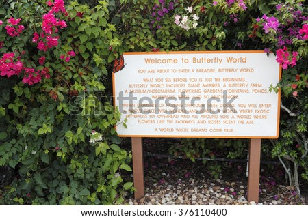 Coconut Creek, FL, USA - July 21, 2015: Welcome to Butterfly World sign located in Tradewinds Park. A Welcome to Butterfly World sign with flowering plants.