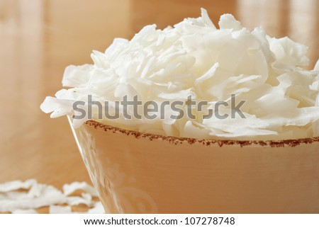 Coconut flakes overflowing from decorative ceramic bowl onto wood table.  Macro with extremely shallow dof. - stock photo