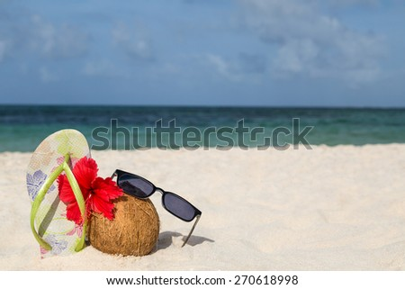 Coconut, hibiscus flower, sunglasses and flip flops on the beach - stock photo