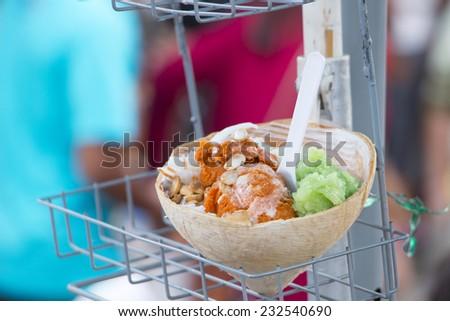 Coconut ice cream in coco shell,multicolored - stock photo
