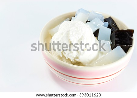 Coconut ice cream topped with black jelly and nata de coco in a bowl.