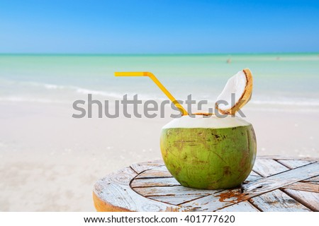 Coconut juice with straw on wood table against blurred beach background.